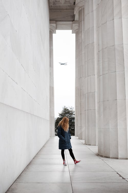 Woman Standing Near Marble Pillars