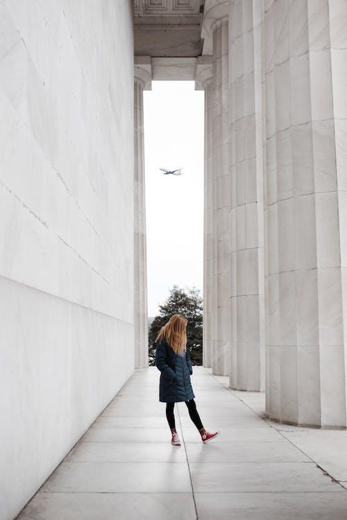 Woman Standing Near Marble Pillars