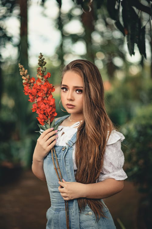 Shallow Focus Photography of Woman Holding Red Flowers