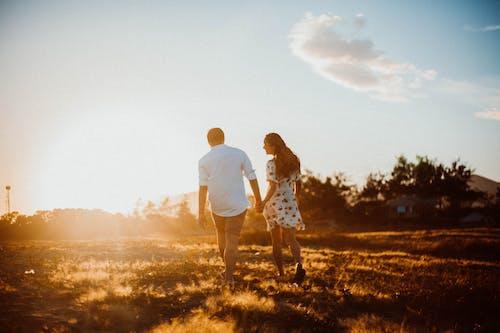 Couple Walking on Grass Field