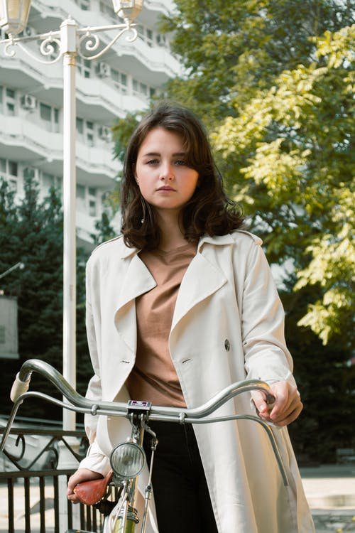 Photo of Woman Wearing White Trench Coat While Holding onto Bicycle