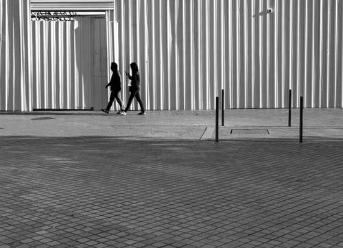 Grayscale Photography of Two Person Walking Beside Wall