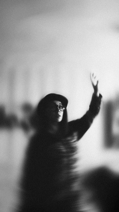 Grayscale Photography of Woman raising her hand