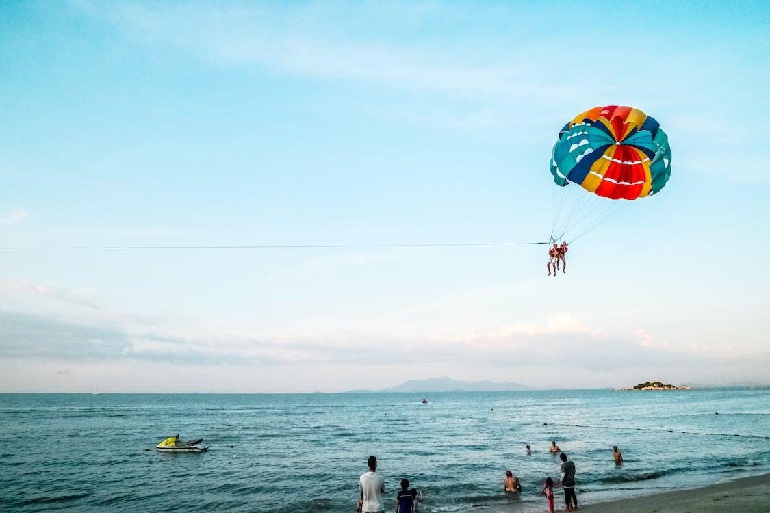 Person Riding Parachute Above Ocean