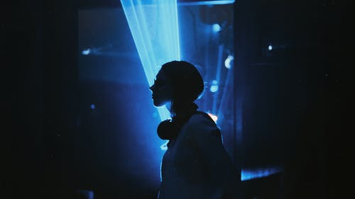 Woman Standing Against Blue Light