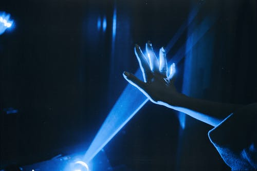 Photo of Person's Hand With Blue Light