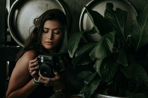 Photo of Woman Holding Black Camera Near Dark Green Plants