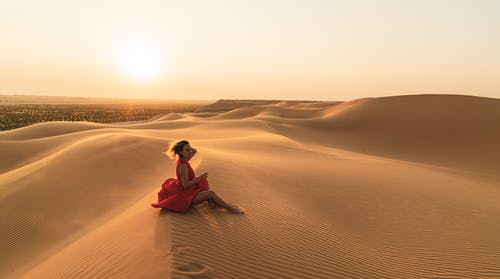 Photo Of Woman Sitting On Sand
