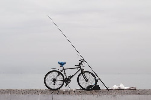 Fishing Rod and Black Bicycle on Concrete Floor