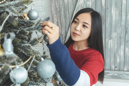 Charming Asian woman decorating Christmas tree