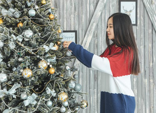 Woman Putting Ornaments on Christmas Tree
