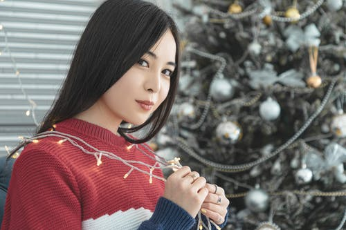 Content Asian woman with garland near decorated Christmas tree