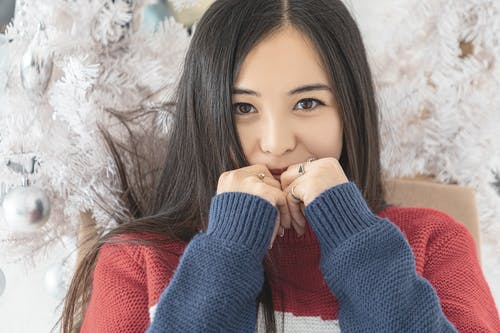 Crop young Asian female wearing cozy sweater standing against white decorated Christmas tree and covering smiling mouth with hands while looking at camera contentedly