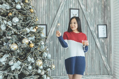 Photo of Woman Standing Near Christmas Tree
