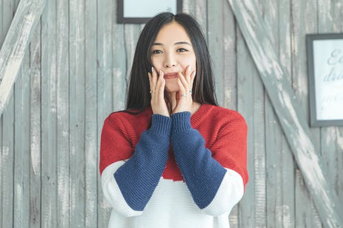Charming Asian woman touching cheeks against wooden wall