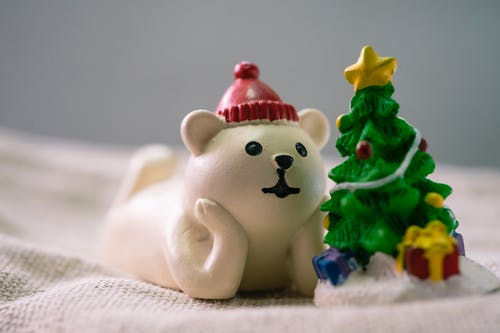 Close-Up Photo of White Polar Bear Beside Christmas Tree Figurines