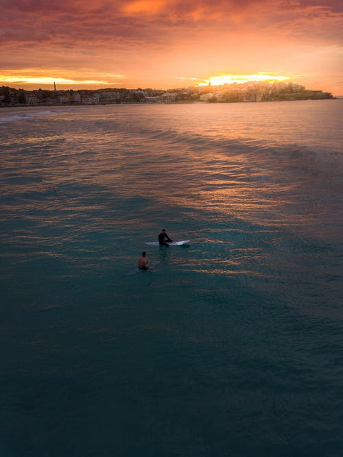 Photo of Two People Surfing in Bondi Beach