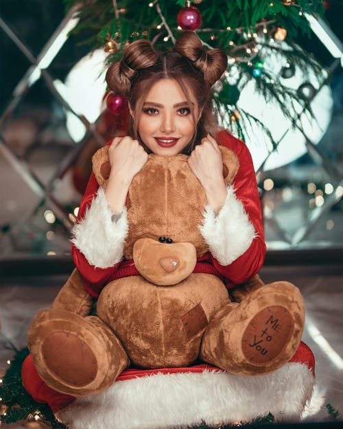 Woman Wearing Santa Costume While Hugging Teddy Bear
