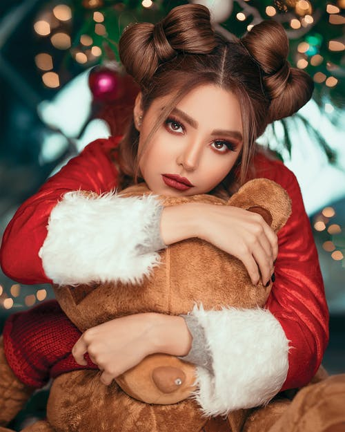 Woman Wearing Santa Costume While Hugging Teddy Bear