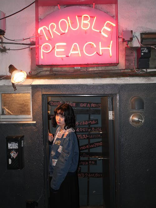 Woman Standing Near Trouble Peach Bar