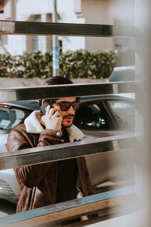 Mężczyzna Nosi Okulary Przeciwsłoneczne Podczas Korzystania Z Telefonu Komórkowego