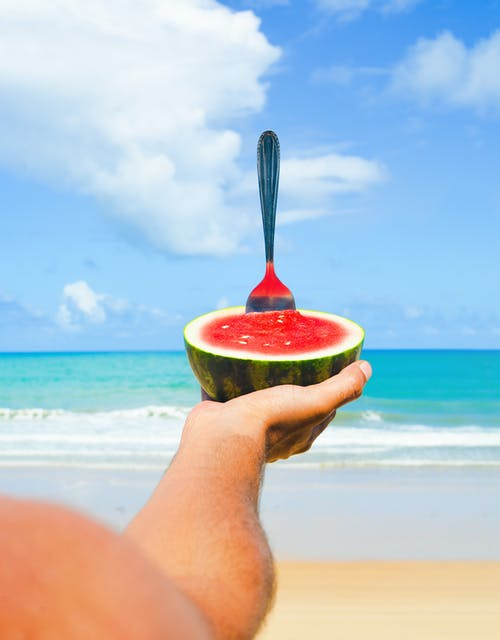 A Man Holding A Watermelon Under The Blue Sky