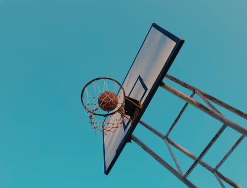 Basketball and Backboard Under Blue Sky