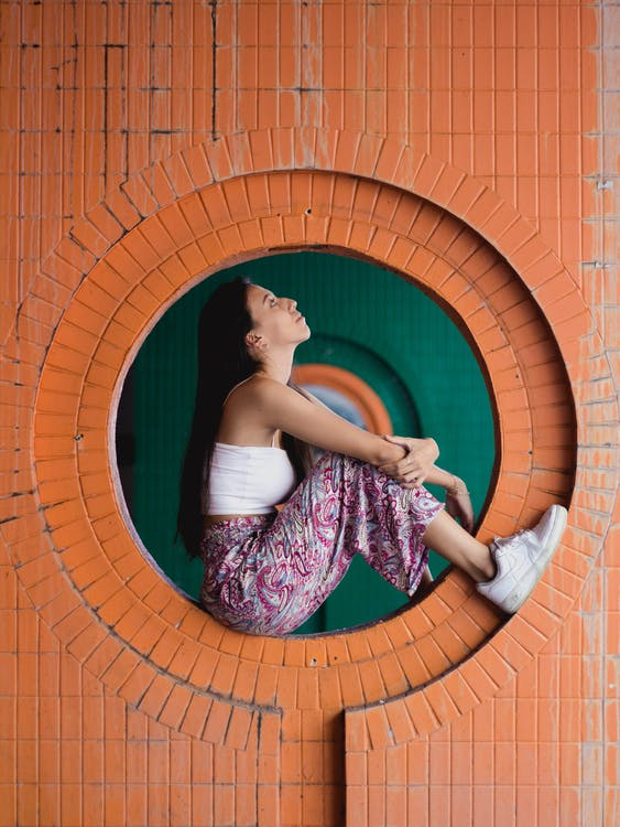 Woman Sitting in Wall Hole