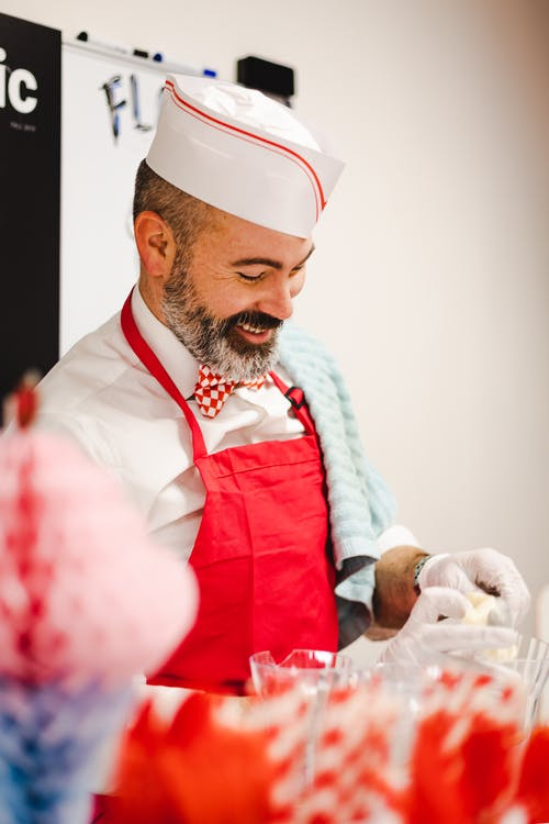 A Chef In Red Apron With A Smile On His Face