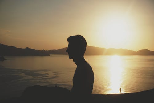 Silhouette of Man Facing Calm Sea