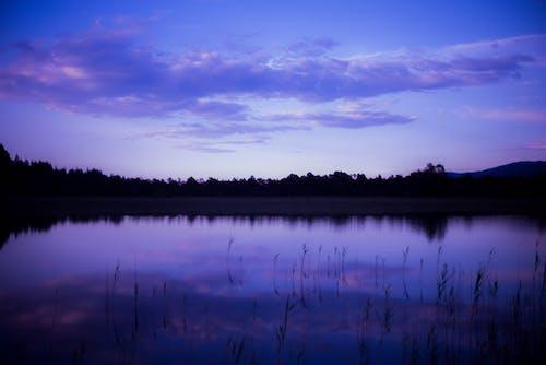 Body of Water Under Purple Sky