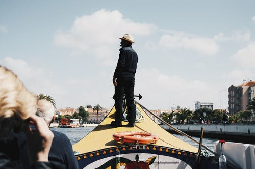 Black man standing on tourists boat front