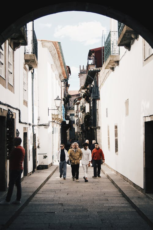 Full body group of faceless people in casual outfits strolling along narrow pedestrian street between cozy white residential houses during sunny day