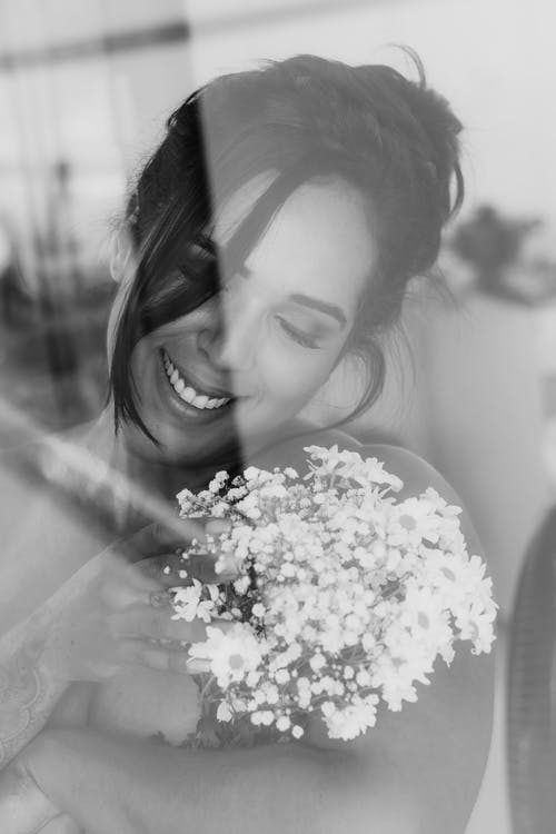 Grayscale Photo of Smiling Woman Holding A Bouquet Of White Flowers