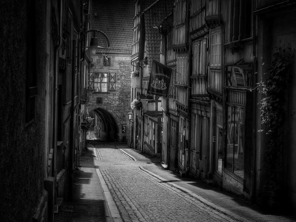 Grayscale Photo of Pathway Inbeetween of Buildings