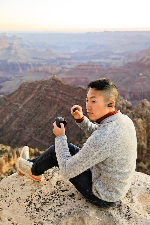 Foto d'estoc gratuïta de a l'aire lliure, assegut, auriculars, aventura