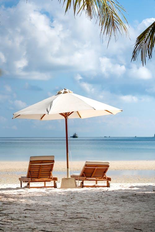 Due Poltrone In Legno Marroni Accanto All'ombrellone Vicino Alla Spiaggia