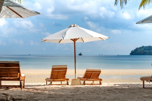 Tropical beach with deckchairs and umbrella