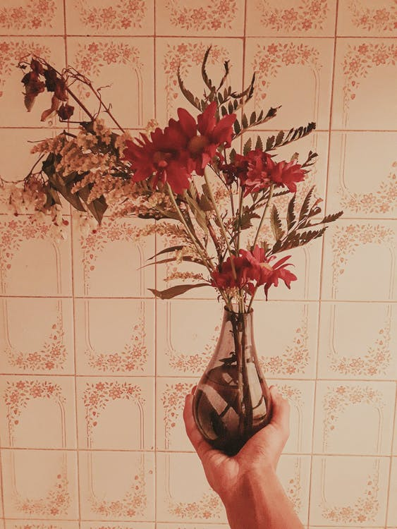Crop person holding bunch of delicate fresh flowers in glass vase near tile wall
