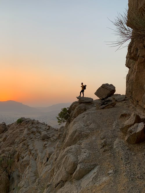 Person Standing on Rock