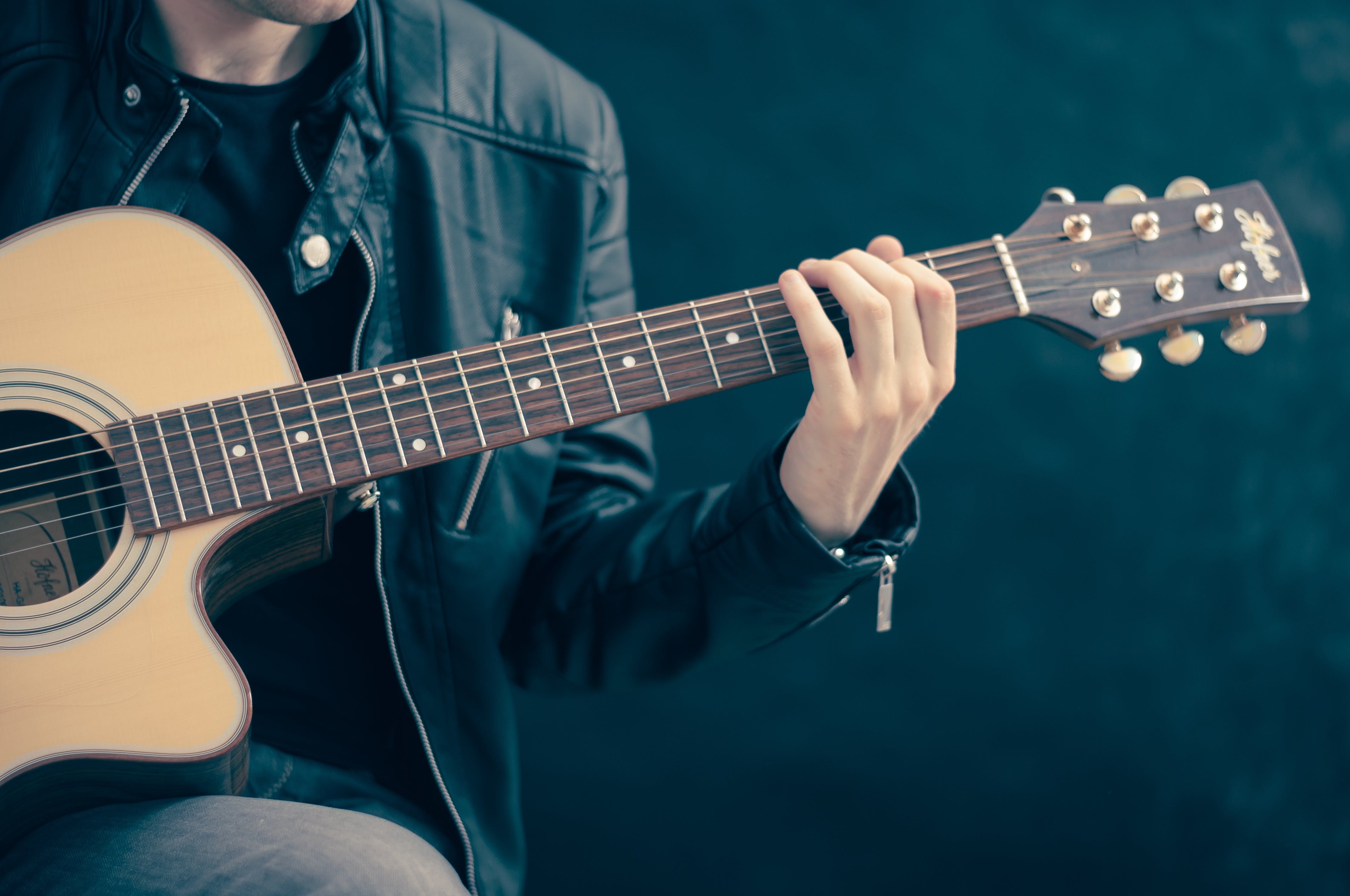 Person Holding Brown and Black Guitar