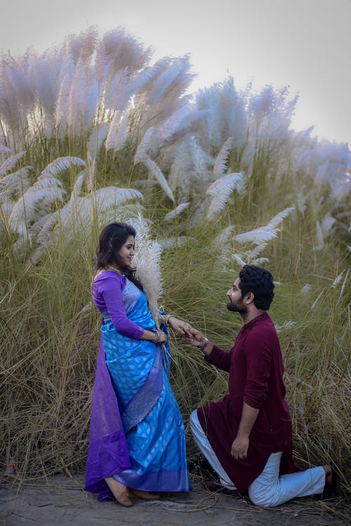 Side view of happy young bearded Indian man standing on knee and making marriage proposal to girlfriend in traditional dress near blooming field