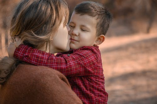 Young mother kissing cute sons cheek in nature