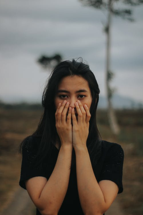 Woman Covering Her Face Using Both Hands