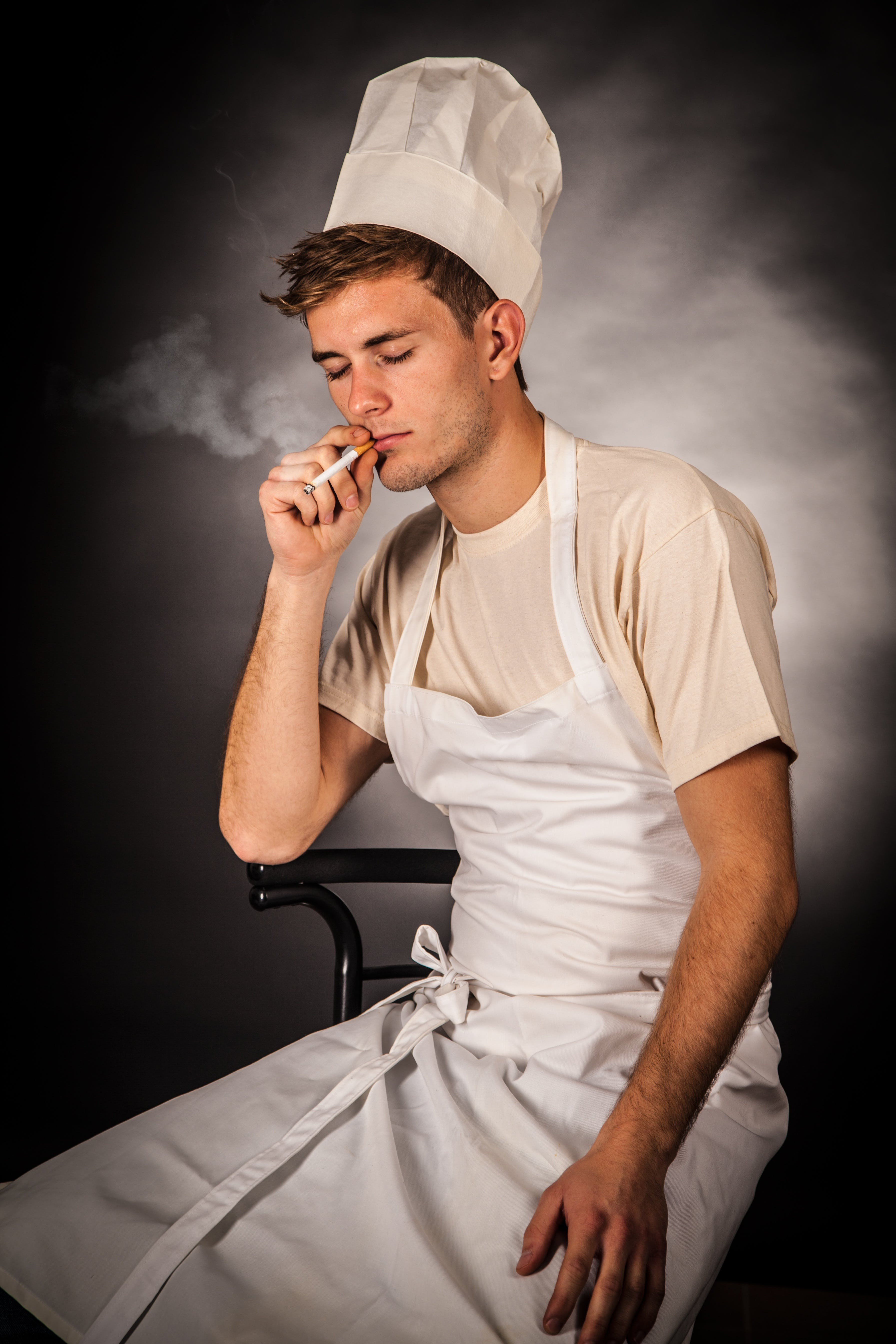 Man in White Apron Holding Cigarette Smoking