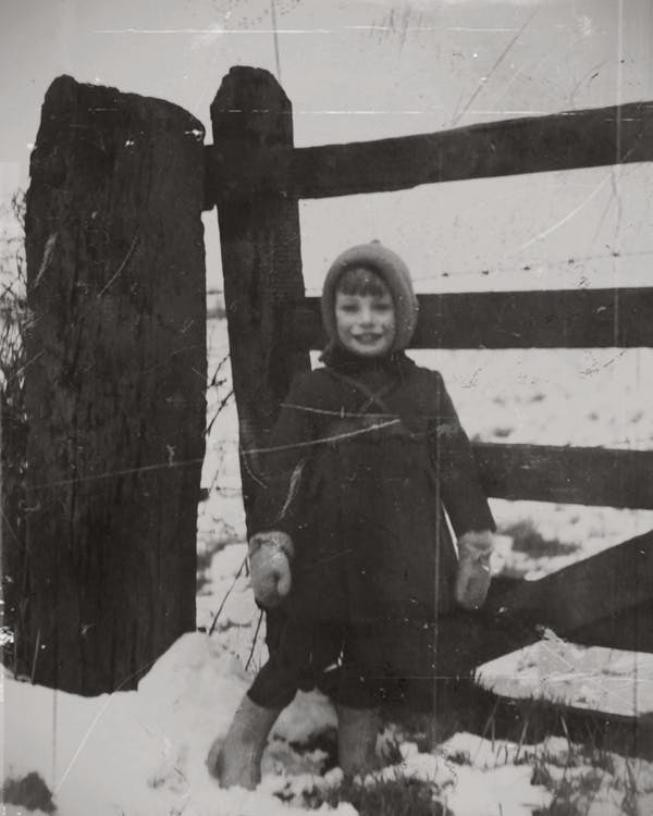 Grayscale Photography Of A Child Standing On Snow Beside a Wooden Fence