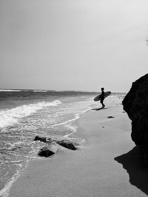 Grayscale Photo of Person Standing on Seashore Holding Surfboard