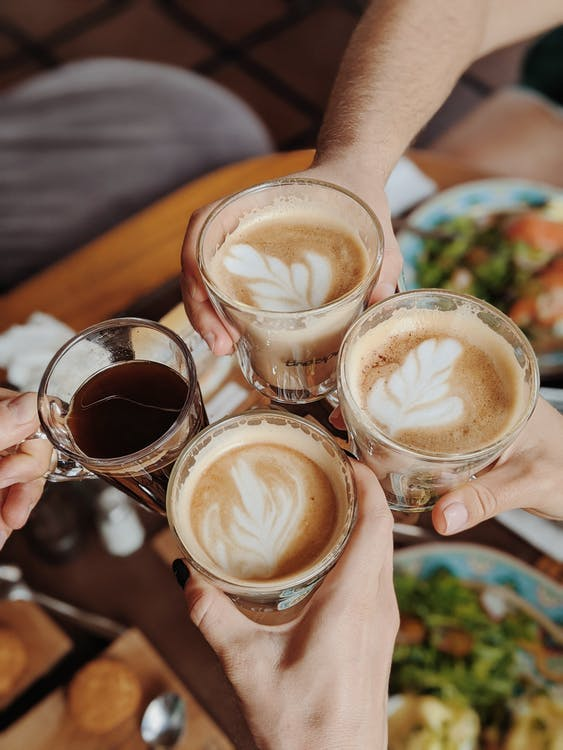 People With Four  Drinking Glasses Of Coffee While Making A Toast