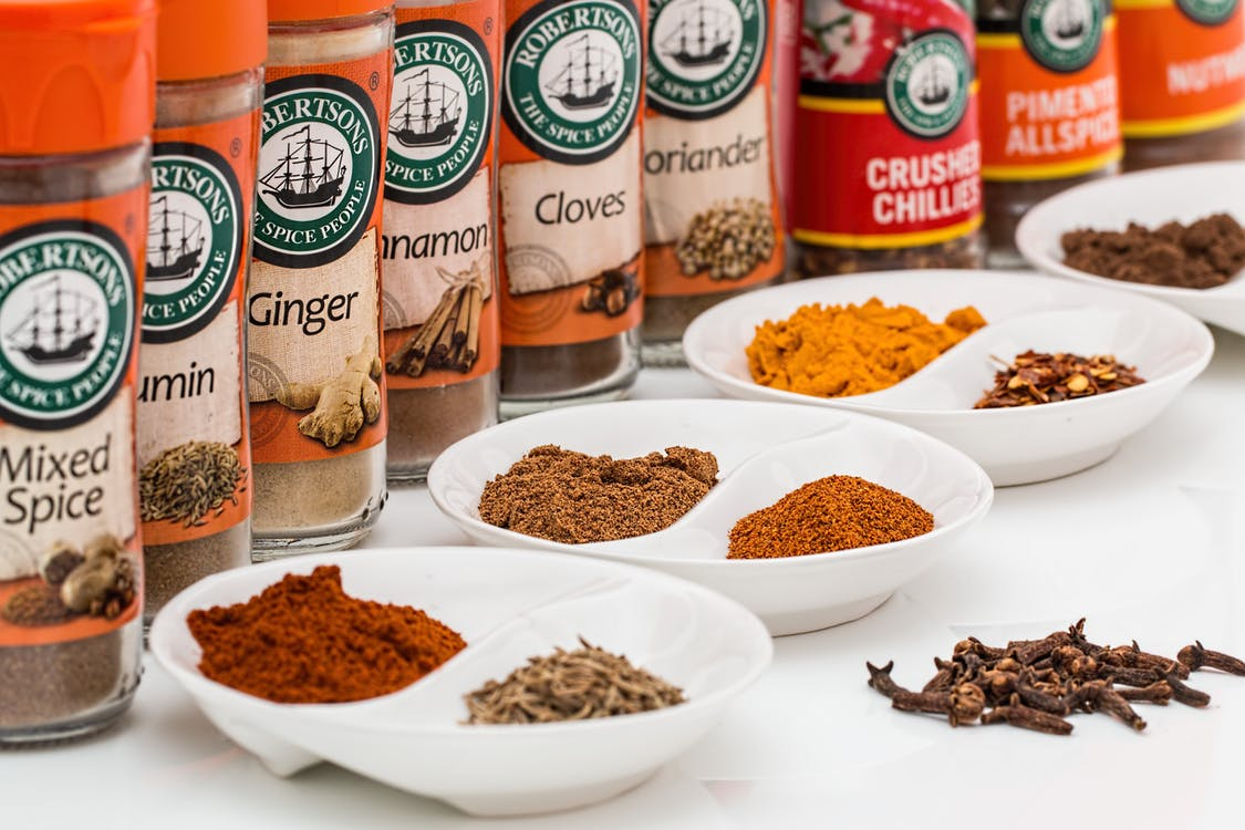 Mixed Spice Bottles on White Surface With Bowls
