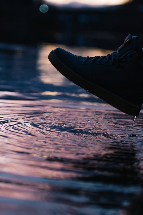 Photo of Person Wearing Shoe Near Body of Water